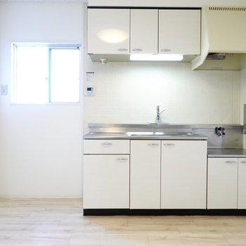 お部屋に合わせた真っ白なパネルのキッチン。窓があるから換気もしやすい◎