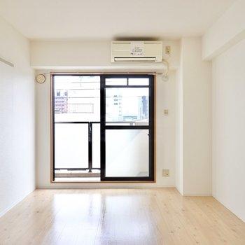 洋室は約8.9帖。木目調の床に合わせた木材のテーブルやベッドフレームがお似合い。