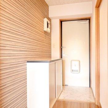 ストライプの壁紙と大理石調のタタキがカッコいい雰囲気の廊下と玄関。