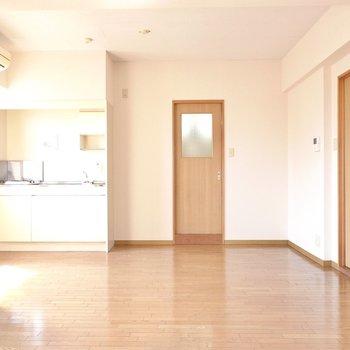 キッチンとリビングをテーブルでゆるっとゾーニングするのも良いですね。正面に見えるのは脱衣所のドア。