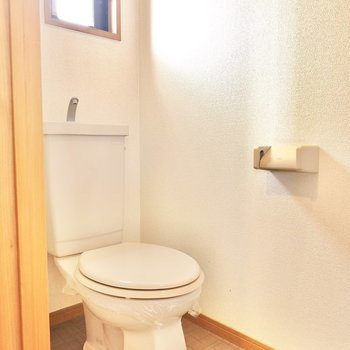 右には窓のある換気のしやすいトイレ。ウォシュレットの後付けができ、収納棚も備え付けです。