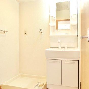 脱衣所の正面には洗濯機置き場と棚付きの洗面台。