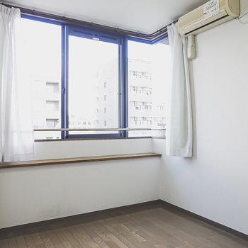 コーナー窓のある明るい洋室。大きめのベッドを置いて寝室に。