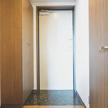 黒くシックな土間の玄関。トイレは右手のドアの先にあります。