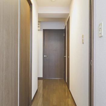 廊下に出て正面が洋室、右奥がトイレ、左手前が脱衣所のドア。