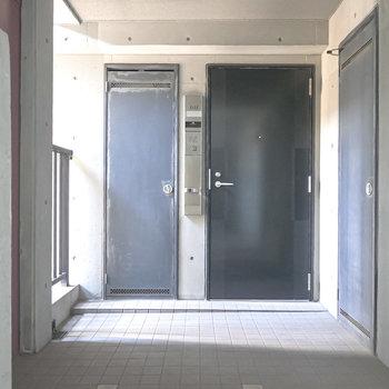 玄関前はコンクリ造で光が映える共用部。
