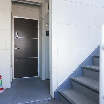 玄関前の共用部。階段を上がって右手にお部屋があります。