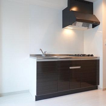 吊り戸棚のないスッキリした見た目の黒いキッチン。
