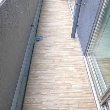 集成材のような模様が清潔な雰囲気のあるベランダ。物干し竿もついています。(※写真は建設中のものです)