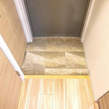 タイル模様がカッコいい玄関。靴箱は左の扉の中に。(※写真は2階の同間取り別部屋のものです)