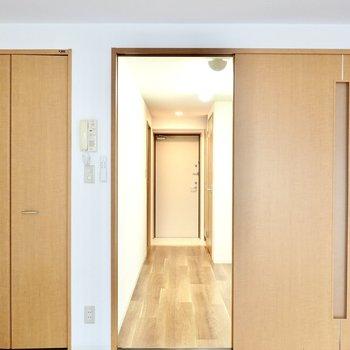 引き戸の先はキッチンスペース。右手にキッチン、正面に玄関。(※写真は1階の反転間取り別部屋のものです)