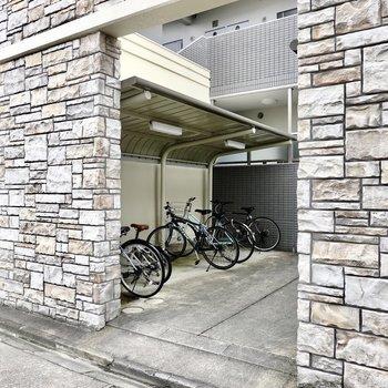 右手には石壁に囲まれた屋根付きの駐輪場。共用部はスタイリッシュですね。