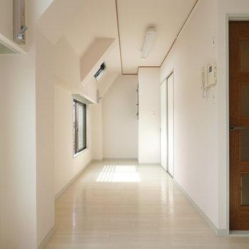 廊下のように伸びたリビングに天窓から光が降り注ぐ。窓辺にダイニングテーブルを置いて。