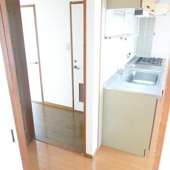 キッチン横の扉から廊下へ。右がトイレ、左が脱衣所へのドア。