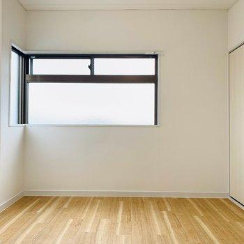 【玄関側洋室】角に沿って曲がる不思議な窓。