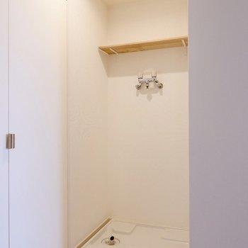 右側には洗濯機置き場が。上部に木板のシェルフがあります。