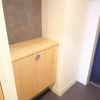 モルタルっぽい風合いの壁のそばには廊下の収納と素材を合わせた靴箱。