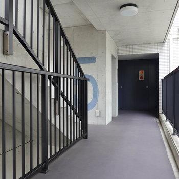 入り組んだコンクリ壁と黒鉄塗装の手すりがさながら建築作品のようなエレベーターホール。