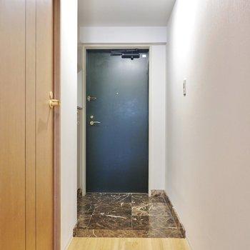 深い青のドアに大理石調のタタキがクール。
