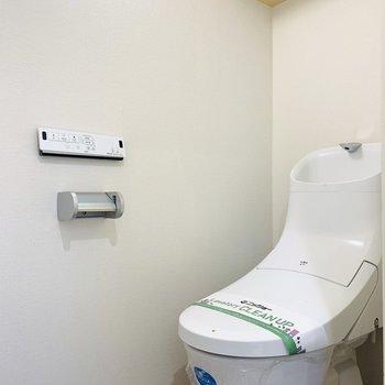 上部に棚がついたウォシュレット付きのトイレ。