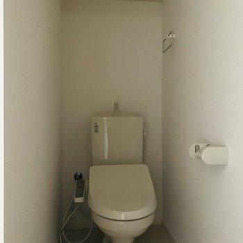 上部に棚のついた、ウォシュレット付きのトイレ。(※お部屋は通電前です。)