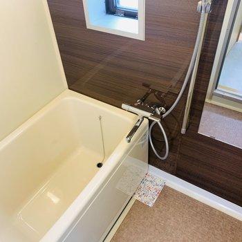 窓のあるバスルーム。広めの浴槽とともに開放感を感じられる。