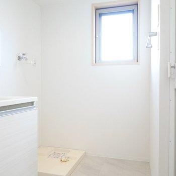 窓付きで明るく換気もできる脱衣所。正面には洗濯機置き場があり…