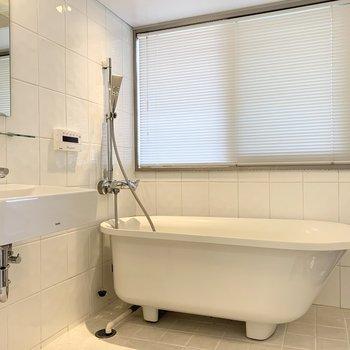 バスルームの主役はかわいいバスタブ◎ブラインド奥のサッシは開閉可能なスモークガラスタイプ。