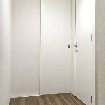 右側はトイレ、左はサニタリーのドアです。(※写真は1階の反転間取り別部屋のものです)
