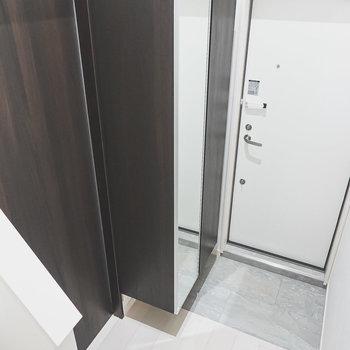 グレーの土間。その隣にはトールサイズの靴箱。左のドアからはトイレへ。