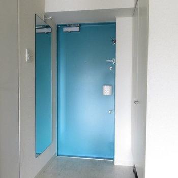 玄関は原色の水色(※写真は11階の同間取り別部屋のものです)