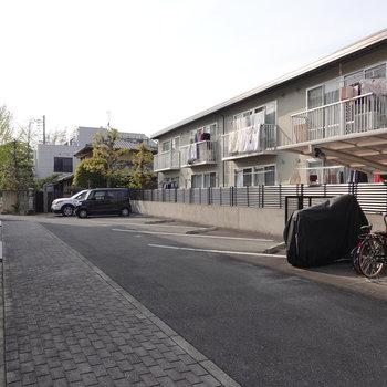 エントランス前には駐輪場と駐車場。左奥にも駐車場があります。