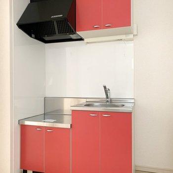 キッチンは素敵な赤色。お隣に冷蔵庫置場も。