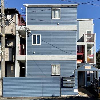 外観は青と打ちっぱなしに赤が映えるお家。