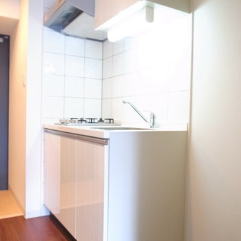 キッチンは白いタイル張りです。右手に冷蔵庫が置けます。