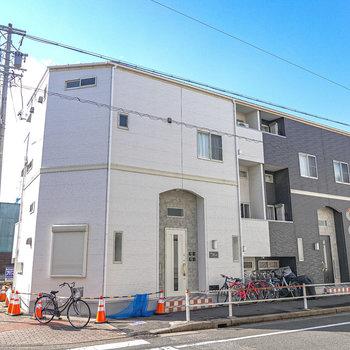 駅を出てすぐ目の前の黒と白の建物。お部屋へは白色の方の玄関から入ります。