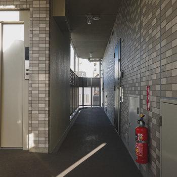玄関前の共用部はタイルでシックに。
