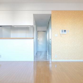 対面式キッチンと黄色ともオレンジともとれる色のアクセントクロスがお部屋を開放的にしています。