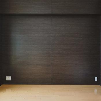 ウォルナット調の壁には大画面のテレビを。その向かいにはウッドフレームソファを。