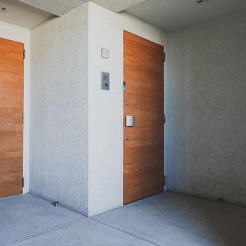 モルタルのような質感の共用部に木目のドアが際立っています。