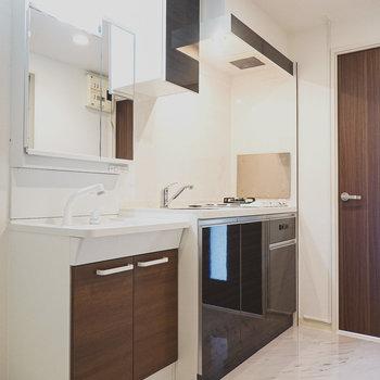 黒いパネルのキッチン。すぐ横には大きな鏡の洗面台!