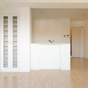 真っ白のキッチンと食器棚。カウンターにはボクを呼ぶキミ。