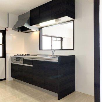 建具とトーンを合わせたピリッとしたキッチン。キッチン脇には冷蔵庫置場。