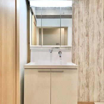 収納付きの洗面台。壁紙もワンポイント。