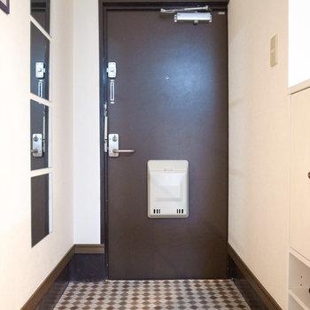 個性的な鏡に目がいく玄関。床のクロスもシックです。