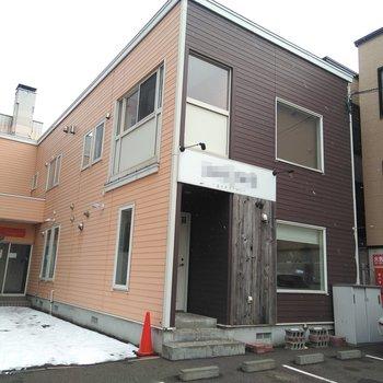 1階部分に美容院がある建物。 入り口は左奥の扉です