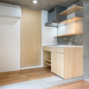 木目調のキッチン。後ろに冷蔵庫などを。