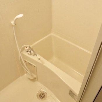お風呂は真っ白。鏡もありますよ! (※写真は9階の反転間取り別部屋のものです)