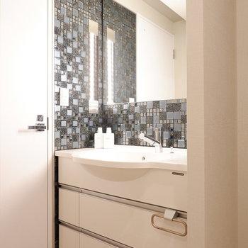 洗面台にもキッチン同様のタイルが用いられ、照明も横に付いています。※家具・雑貨はサンプルです