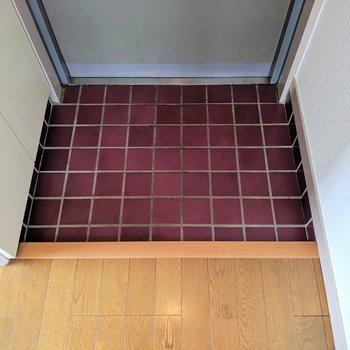 真紅のタイルが貼られた玄関※写真は4階の同間取り別部屋のものです